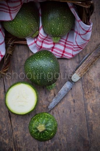 Deutschland, Studio, runde grüne Zucchini auf Holztisch