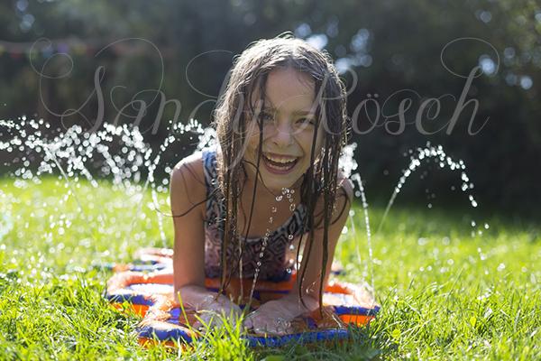 Mädchen hüpft auf einem Wasserhüpfkästchen, Garten, Bayern, Deutschland